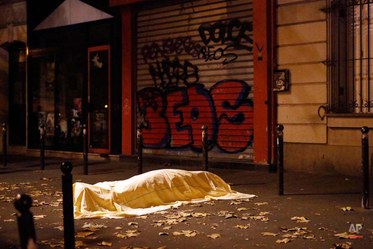 FOR USE AS DESIRED, YEAR END PHOTOS - FILE - A victim of a terrorist attack lays dead outside the Bataclan theater in Paris, Nov. 13, 2015. (AP Photo/Jerome Delay, File)