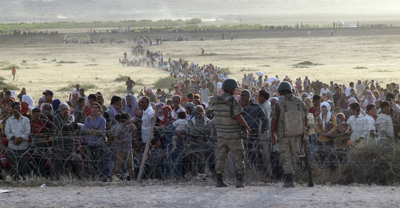 turkish-soldiers-stand-guard-syrian-refugees-wait-behind-border-fences-1